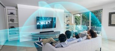Familia en un sofá viendo la TV con la barra de sonido HT-A5000 en un mueble de mármol