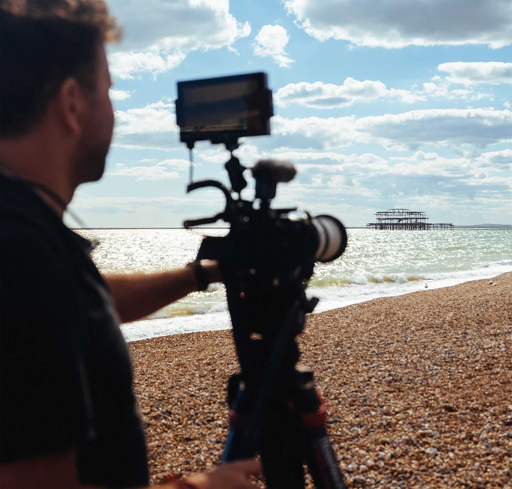 philip bloom filming on the beach with a run down pier in the distance