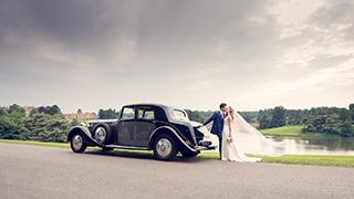 brent-kirkman-sony-alpha-7RIII-newly-married-couple-kiss-and-embrace-next-to-vintage-car