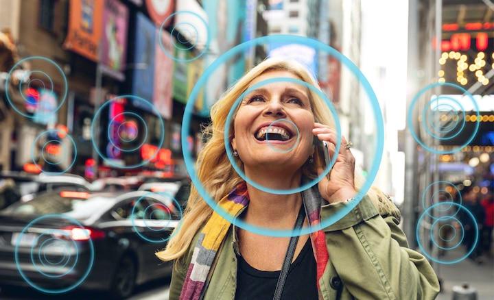 Mujer en escena de calle bulliciosa para demostrar cómo Voice Zoom 2 mejora las voces