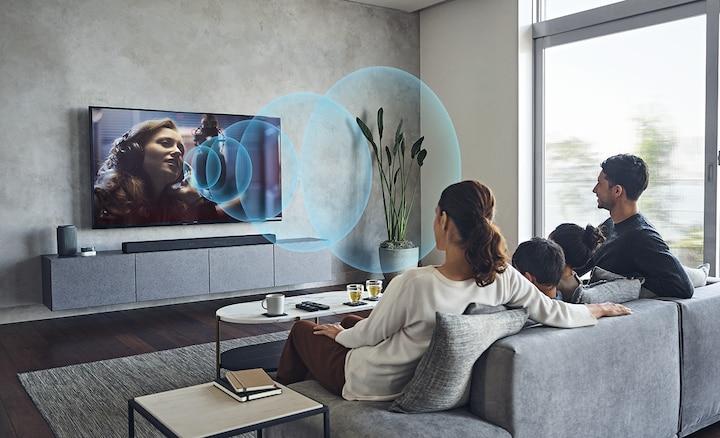 Familia en un sofá viendo la TV con la barra de sonido HT-A7000 en un mueble de mármol