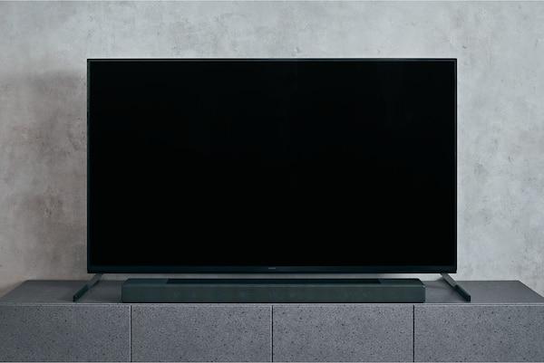 Barra de sonido HT-A7000 en un mueble de mármol bajo un televisor BRAVIA con un soporte multiposición