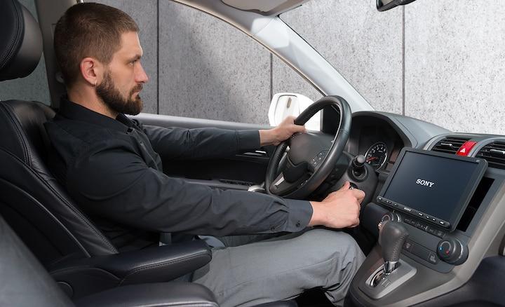 Imagen de un conductor arrancando el coche e iniciando la activación rápida del XAV-AX8050D.
