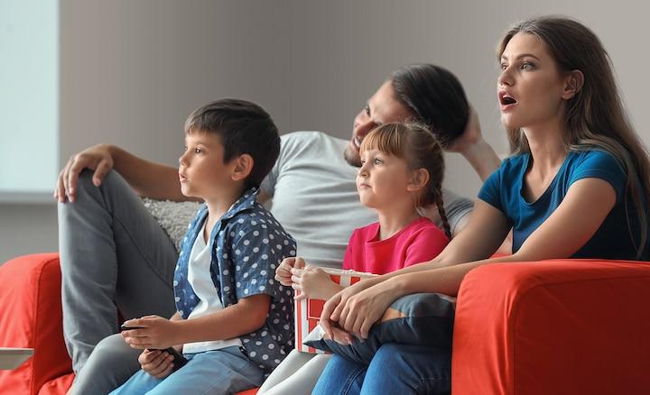 Familia viendo la televisión en un sofá